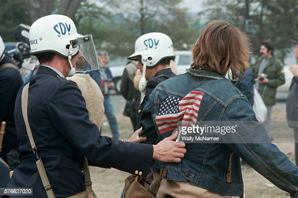 An antiwar demonstrator arrested while participating in the May Day protests in Washington DC is escorted to detention by a Metropolitan Police Civil...