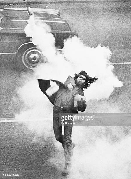 An antiwar demonstrator at the University of California Berkeley throws a tear gas cannister at police during a student strike to protest the killing...