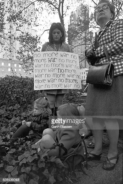An antiwar demonstrator holds a sign as she looks at a pair of young girls seated in an ivy patch in Bryant Park during a Vietnam War protest New...