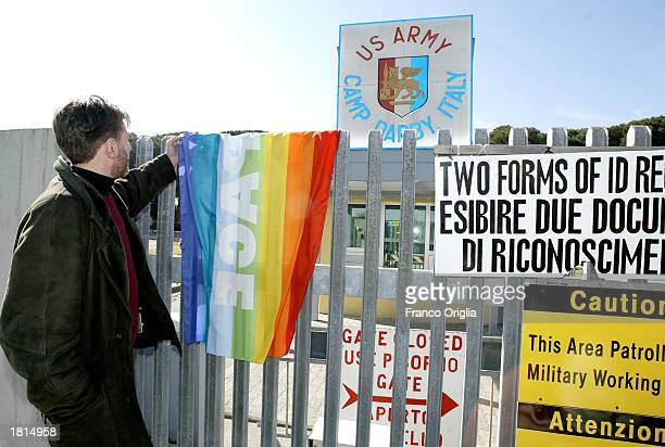 An antiwar demonstrator holds up a rainbow peace flag in front of Camp Darby US military base February 25 2003 near Pisa Italy Demonstrators from The...