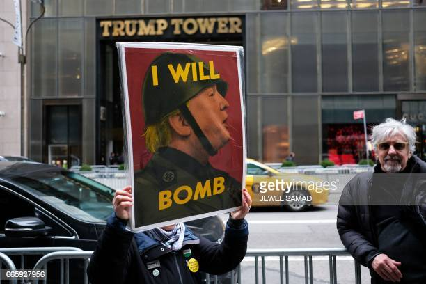 An antiwar protester displays a placard against US President Donald Trump during a demonstration in front of the Trump Tower in New York on April 7...