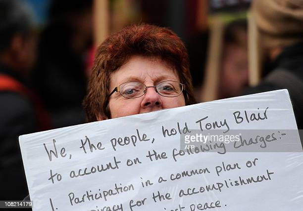 An anti-war protestor holds a placard during a demonstration outside the Queen Elizabeth II Conference Centre in central London, as former British...