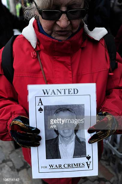 An anti-war protestor holds a sign outside the Queen Elizabeth II Conference Centre in central London, as former British Prime Minister Tony Blair...