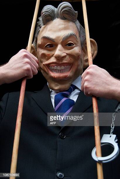 An anti-war protestor wears a mask of former British Prime Minister Tony Blair as he stands in a mock prison cell outside the Queen Elizabeth II...