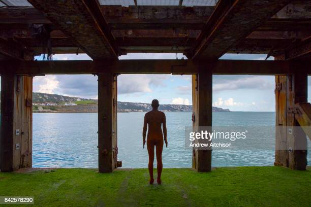 An Antony Gormley cast iron figure from the series Another Time located on the half tide loading bay of the Folkestone Harbour Arm Part of the 2017...