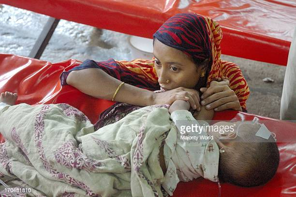 An anxious mother sits beside her diarrhea affected child at ICDDRB Hospital in Dhaka August 14 2007