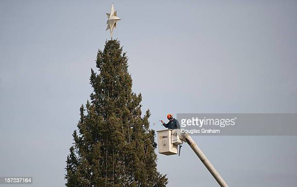 An AOC worker using a cherry picker puts lights on the US Capitol Christmas Tree on the West Front November 30 2012