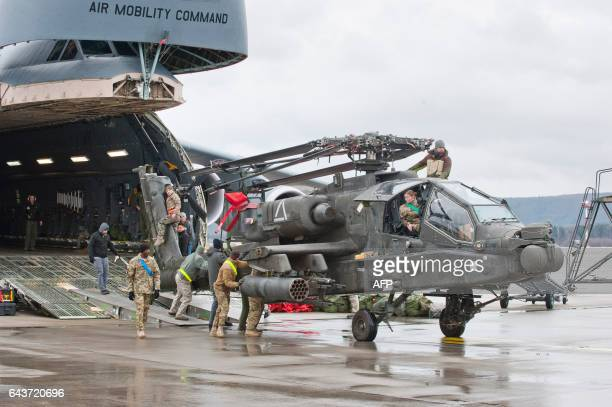 An Apache attack helicopter is being unloaded from a Galaxy C5 transport plane at the US Air Base in Ramstein western Germany on February 22 2017 The...