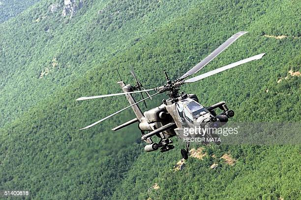 An Apache helicopter flies over the Yugoslav province of Kosovo as they provide security to NATO convoys entering the region 13 June 1999 US Army has...