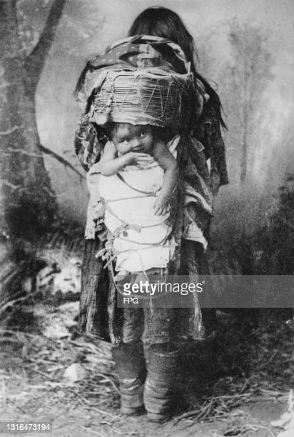 An Apache Indian woman carry a baby using an animal skin basket as a baby carriage fastening it on her back, US, circa 1930.