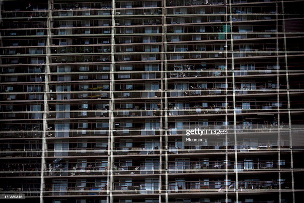 An apartment building is reflected in a glass window in Winnipeg, Manitoba, Canada, on Thursday, July 4, 2013. Canada extended the longest streak of merchandise trade deficits in a quarter century in May, with the shortfall narrowing as imports fell faster than exports. Photographer: Brent Lewin/Bloomberg via Getty Images