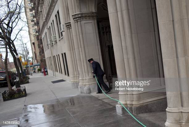 An apartment building security guard washes down a sidewalk March 24 2012 in New York City