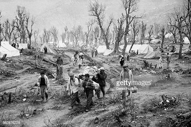 An apocalyptic scene at the Isikveren refugee camp where bare trees lend an eerie atmosphere to a scene in which Kurdish men transport a sick woman...