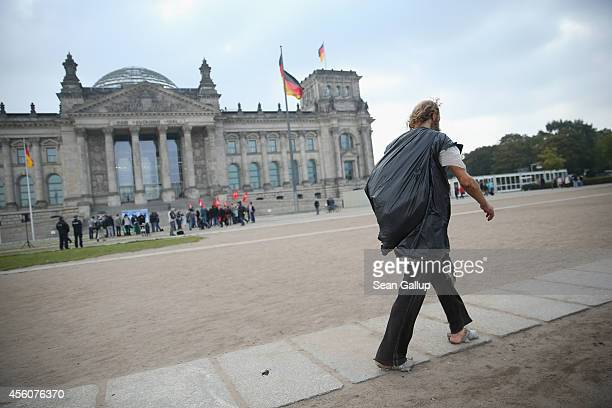 An apparently homeless man wearing plastic wrapped around his bare feet and a plastic garbage bag against the elements walks past the Reichstag on...