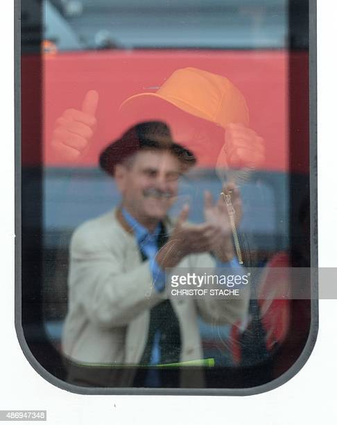 An applauding man is reflected in a window of a train in which a refugee sits at the main train station in Munich southern Germany September 05 2015...