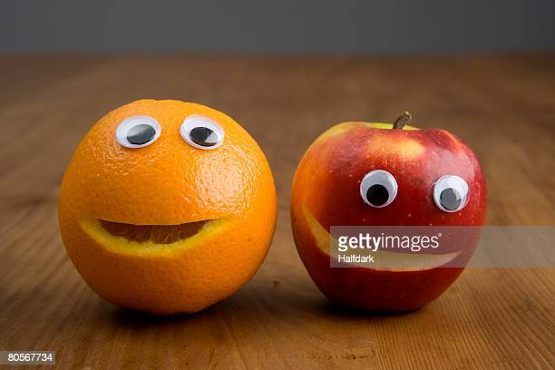 An apple and an orange with plastic eyeballs