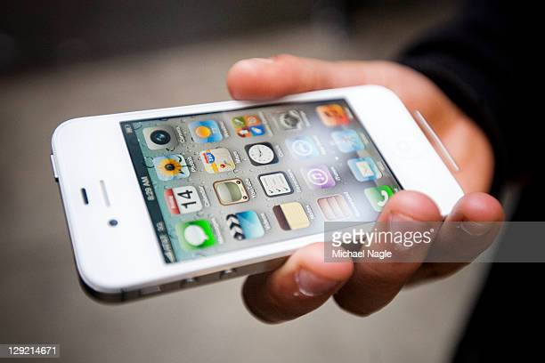 An Apple customer displays his newly purchased iPhone 4s outside of the Apple Store on Broadway and 67th Street on October 14 2011 in New York City...