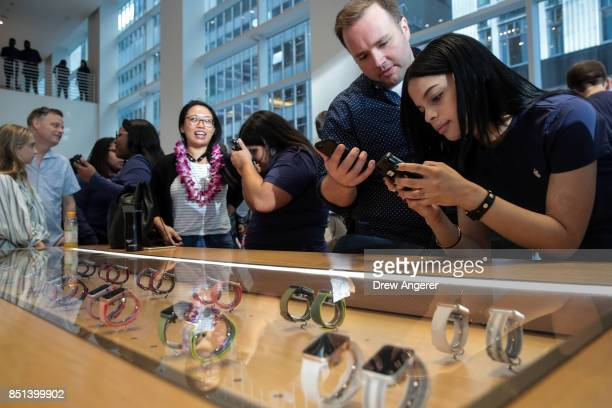 An Apple employee assists a customer with the new Apple Watch Series 3 at the Fifth Avenue Apple Store September 22 2017 in New York City The new...