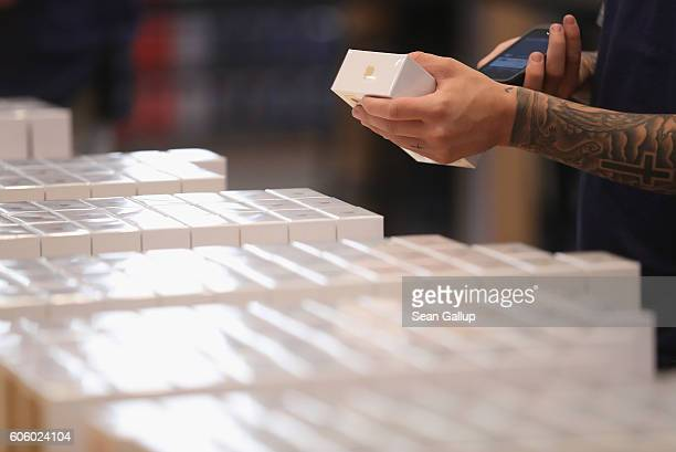An Apple employee checks Apple iPhone 7 phones on the first day of sales of the new phone at the Berlin Apple store on September 16 2016 in Berlin...