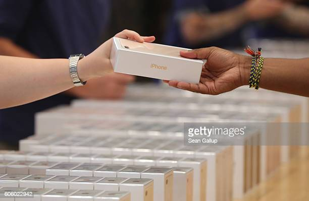 An Apple employee hands over Apple iPhone 7 phones on the first day of sales of the new phone at the Berlin Apple store on September 16 2016 in...