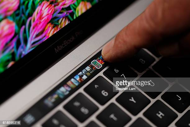 An Apple employee points to the Touch Bar on a new Apple MacBook Pro laptop during a product launch event on October 27 2016 in Cupertino California...