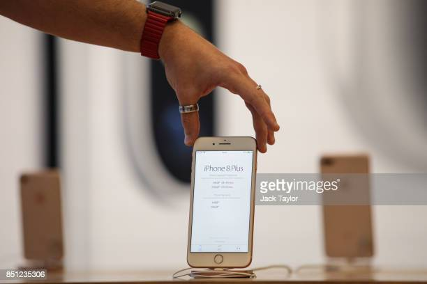An Apple employee poses with the iPhone 8 on display at Apple Regent Street during the launch of the new phone on September 22 2017 in London England...