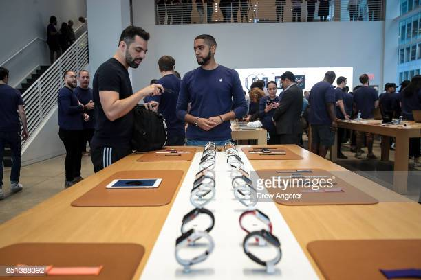 An Apple employee shows a customer the Apple Watch Series 3 at the Fifth Avenue Apple Store September 22 2017 in New York City The new iPhone 8 and...