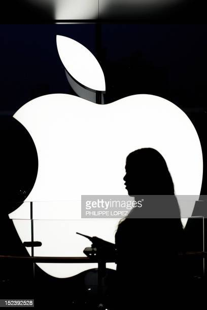 An Apple employee stands in front of the company's logo in the Hong Kong Apple store on September 20 2012 The iPhone 5 will debut on September 21...