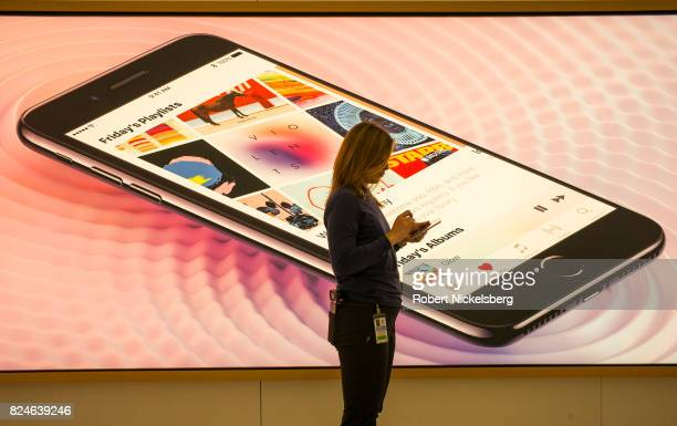An Apple employee uses her iPhone while standing in front of an advertisement at the Apple retail store July 22 2017 at the World Trade Center in New...