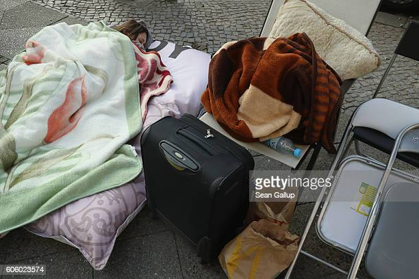 An Apple fan sleeps on a mattress on the sidwalk outside the Berlin Apple store prior to the first day of sales of the new iPhone 7 on September 16...