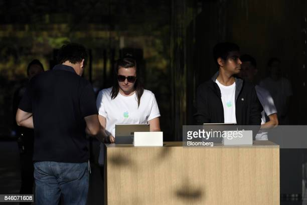 An Apple Inc employee assists an attendee with checkin ahead of an event at the Steve Jobs Theater in Cupertino California US on Tuesday Sept 12 2017...