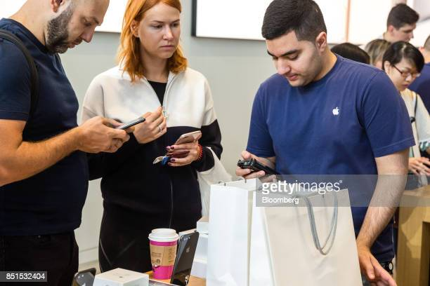 An Apple Inc employee assists customers with their purchases during the sales launch of the iPhone 8 smartphone Apple watch series 3 device and Apple...