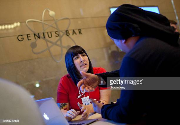 An Apple Inc employee at the 'Genius Bar' works with a customer during the opening of the new Grand Central Station location in New York US on Friday...