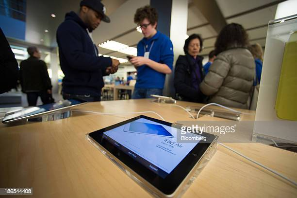 An Apple Inc employee center helps a customer on the first day of sales of the new iPad Air at the 5th Avenue Apple store in New York US on Friday...