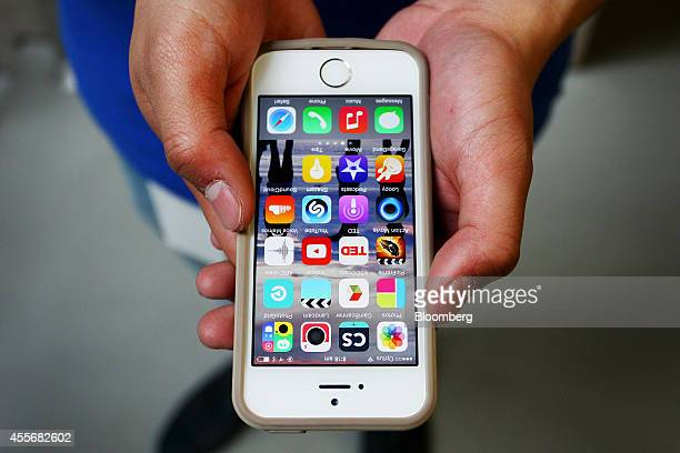An Apple Inc. Employee holds an iPhone 6 for a photograph during the sales launch of the iPhone 6 and iPhone 6 Plus at the company's George Street...
