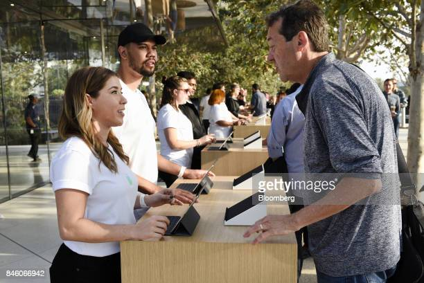 An Apple Inc employee left assists an attendee with checkin ahead of an event at the Steve Jobs Theater in Cupertino California US on Tuesday Sept 12...