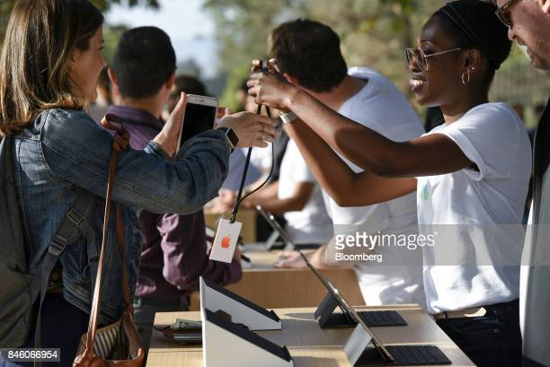 An Apple Inc employee right hands a badge to an attendee ahead of an event at the Steve Jobs Theater in Cupertino California US on Tuesday Sept 12...
