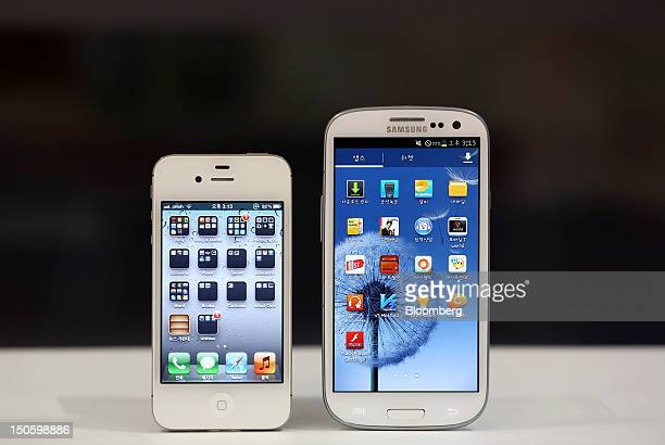An Apple Inc iPhone 4S smartphone left and a Samsung Electronics Co Galaxy S III smartphone are arranged for a photograph in Seoul South Korea on...