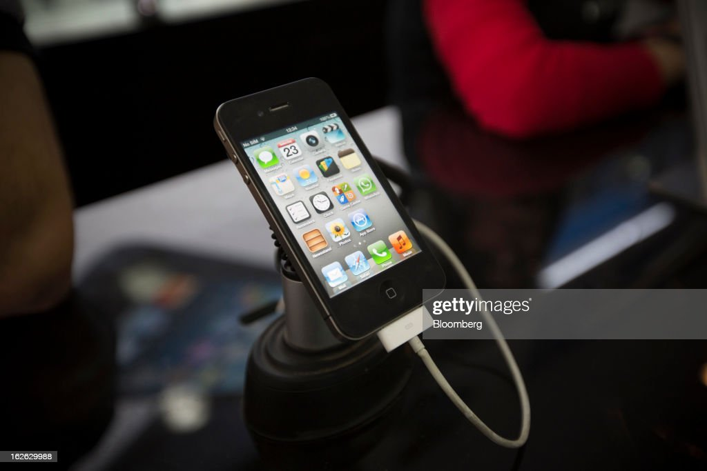 An Apple Inc. iPhone 5 sits on display at a store in Connaught Place in New Delhi, India, on Saturday, Feb. 23, 2013. Finance Minister Palaniappan Chidambaram, who will present his annual budget to parliament on Feb. 28, will seek to narrow the shortfall to 4.8 percent of gross domestic product in the year starting April, from this year's goal of 5.3 percent, according to a Bloomberg survey of analysts and investors. Photographer: Brent Lewin/Bloomberg via Getty Images