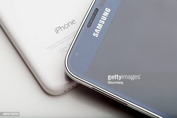 An Apple Inc iPhone 5c left and Samsung Electronics Co Galaxy S5 smartphone are arranged for a photograph in Hong Kong China on Wednesday May 14 2014...