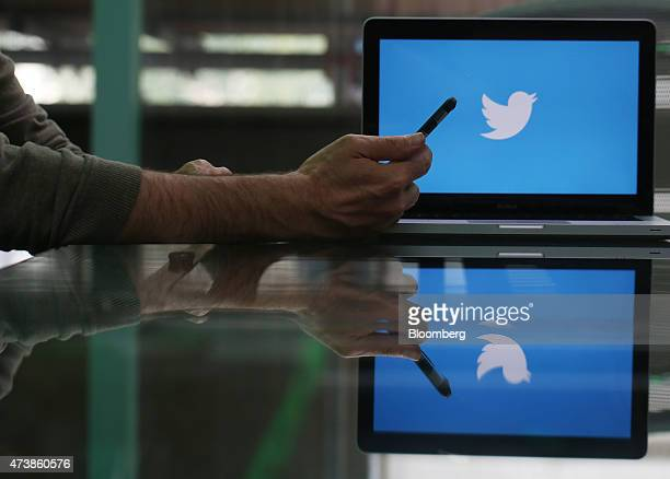 An Apple Inc iPhone 6 smartphone is held as a laptop screen shows the Twitter Inc logo in this arranged photograph taken in London UK on Friday May...