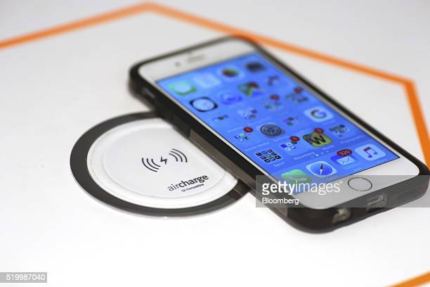 An Apple Inc iPhone rests on an air charge device inside the Smart Home section at a John Lewis Plc department store in London UK on Friday April 8...