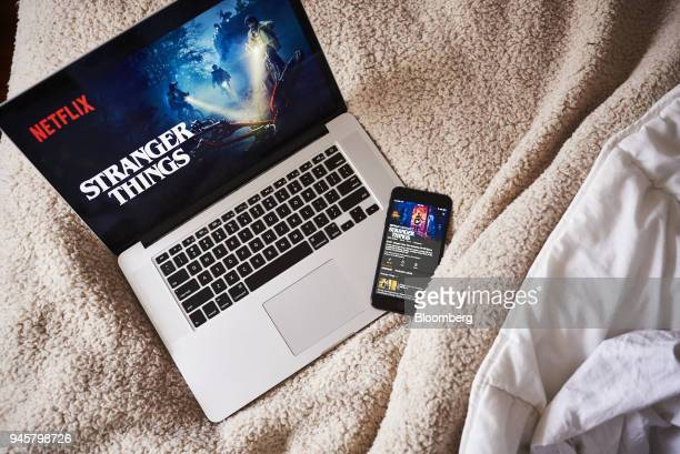 An Apple Inc. Laptop computer and iPhone display the home screen for the Netflix Inc. Original series 'Stranger Things' in an arranged photograph...