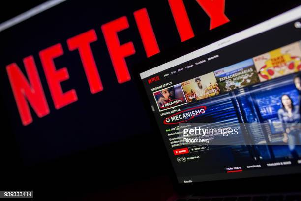 An Apple Inc laptop displays the home screen for the Netflix Inc original series 'The Mechanism' next to signage on a television monitor in an...