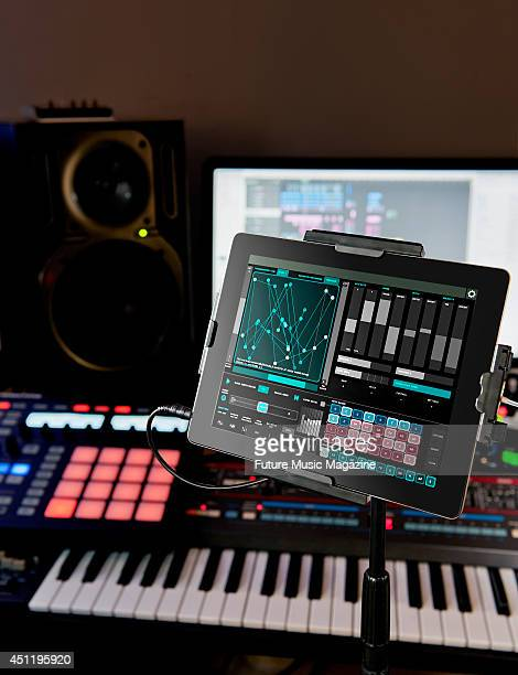 An Apple iPad connected to a selection of studio recording equipment including a keyboard synthesizer photographed for a feature on iOS and recording...