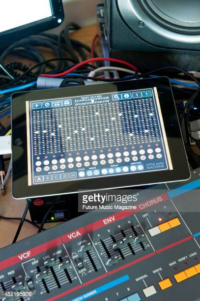An Apple iPad connected to a selection of studio recording equipment including a Roland Juno 106 synthesizer photographed for a feature on iOS and...