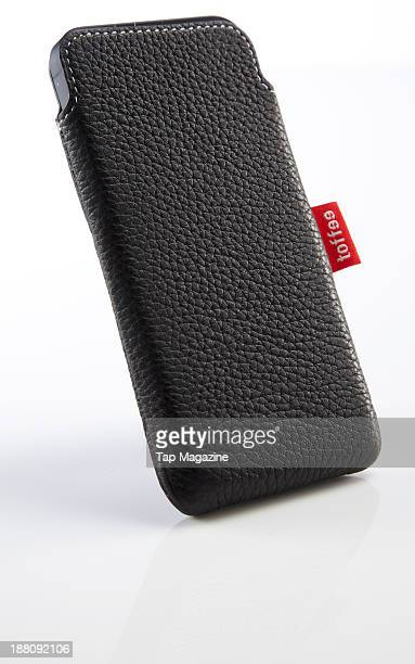 An Apple iPhone 5 with a toffee leather slip case photographed on a white background taken on March 7 2013