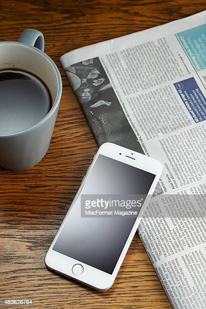 An Apple iPhone 6 alongside a newspaper and cup of coffee taken on October 3 2014