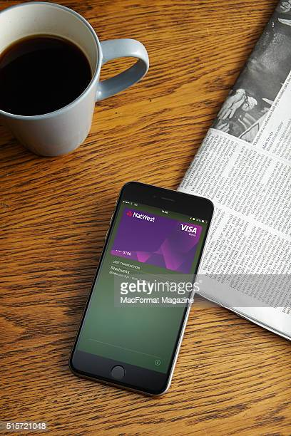 An Apple iPhone 6 with the Apple Pay app visible onscreen alongside a newspaper and cup of coffee taken on October 3 2014