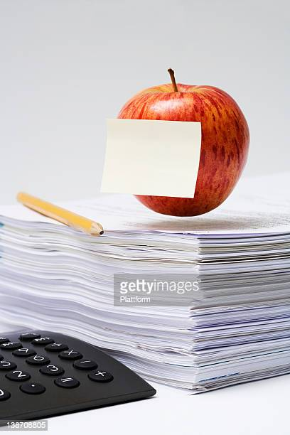 An apple on a stack of paper, close-up.